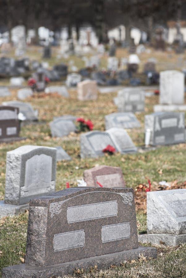 Marcador da lápide do local grave no cemitério do cemitério com flores e mais lápides no vertical do fundo imagem de stock
