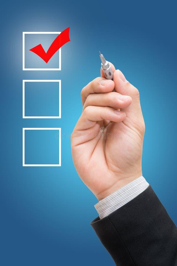 Marcador de la lista de control de la marca de comprobación del hombre de negocios aislado en fondo azul imagen de archivo