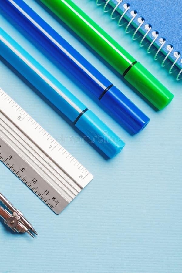 Marcadores, compases, reglas y cuadernos en un fondo azul foto de archivo libre de regalías