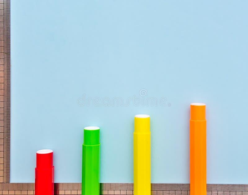 Marcadores e réguas coloridos em claro - fundo azul foto de stock