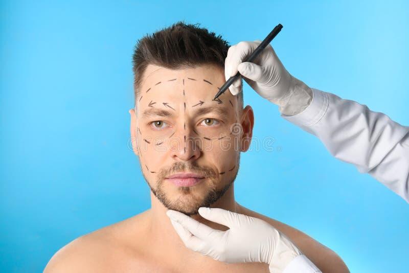 Marcas de dibujo del doctor en la cara del hombre para la operación de la cirugía cosmética contra azul foto de archivo libre de regalías