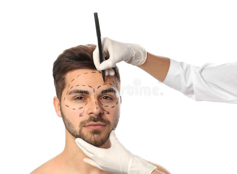 Marcas de dibujo del doctor en la cara del hombre para la operación de la cirugía cosmética contra blanco imagen de archivo
