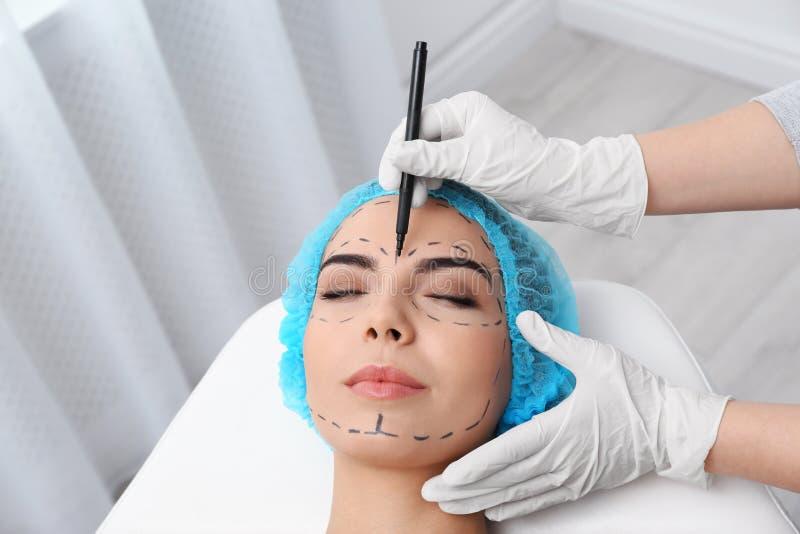 Marcas de dibujo del doctor en la cara de la mujer para la operación de la cirugía cosmética fotos de archivo
