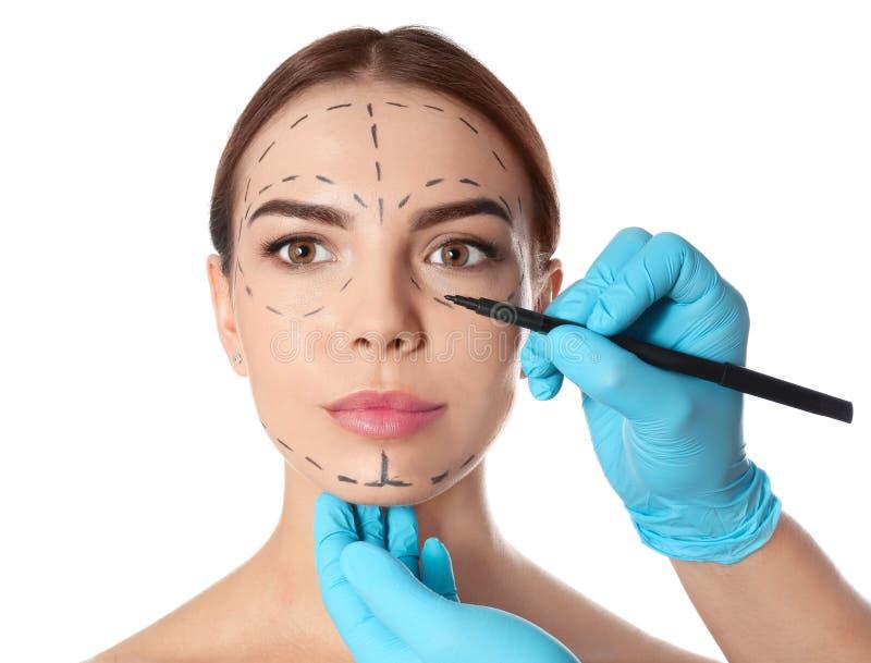 Marcas de dibujo del doctor en la cara de la mujer para la operación de la cirugía cosmética contra blanco fotografía de archivo
