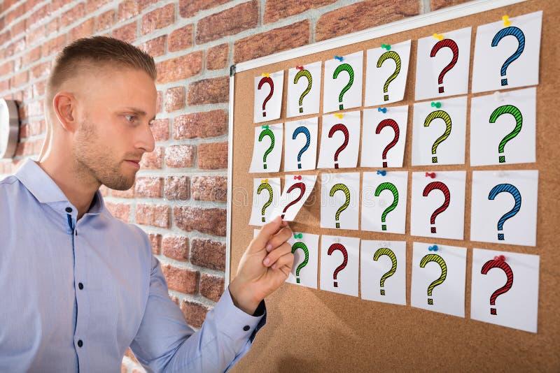 Marcas de Looking At Question do homem de negócios em notas fotos de stock