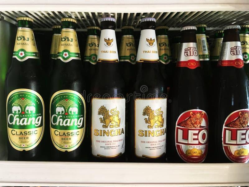 Marcas populares tailandesas de las botellas de cerveza puestas en estante en refrigerador imagenes de archivo