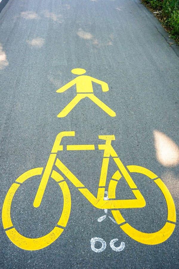Marcature gialle del pedone e della bicicletta sulla via fotografia stock