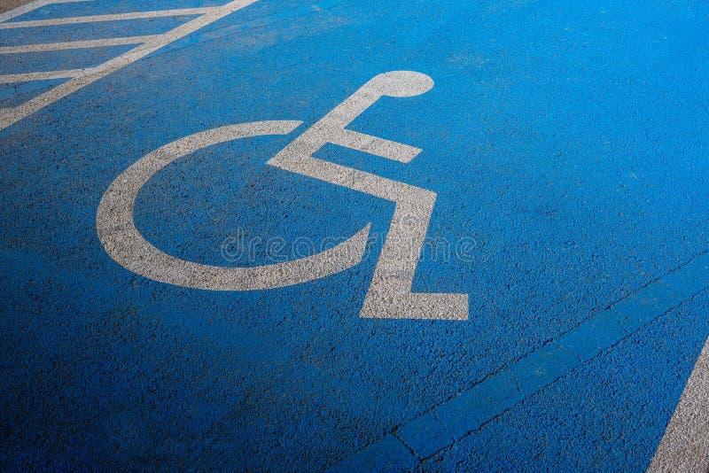Marcature internazionali per un parcheggio handicappato, segno disabile di simbolo su asfalto blu nel posto-macchina immagini stock libere da diritti