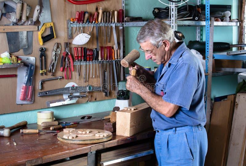 Marceneiro que cinzela a madeira com um formão e um martelo na bancada imagem de stock royalty free