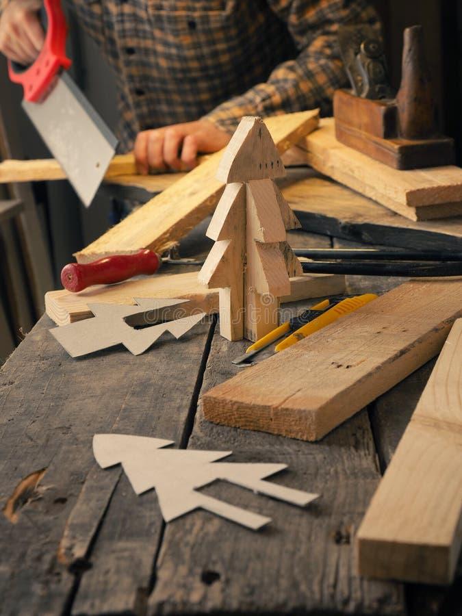 Marceneiro que faz uma decoração de madeira do Natal fotografia de stock