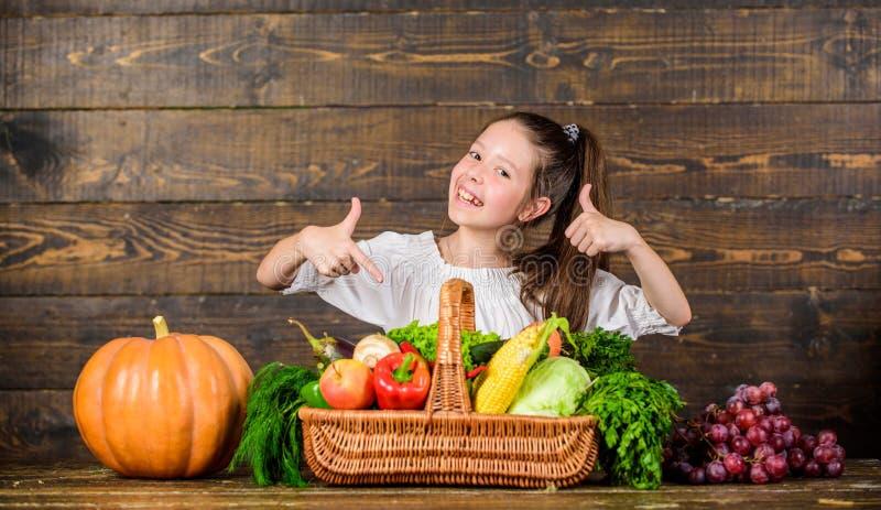 Marché rustique d'agriculteurs de style d'enfant de fille avec l'agriculteur d'enfant de récolte de chute avec le fond en bois de photo stock