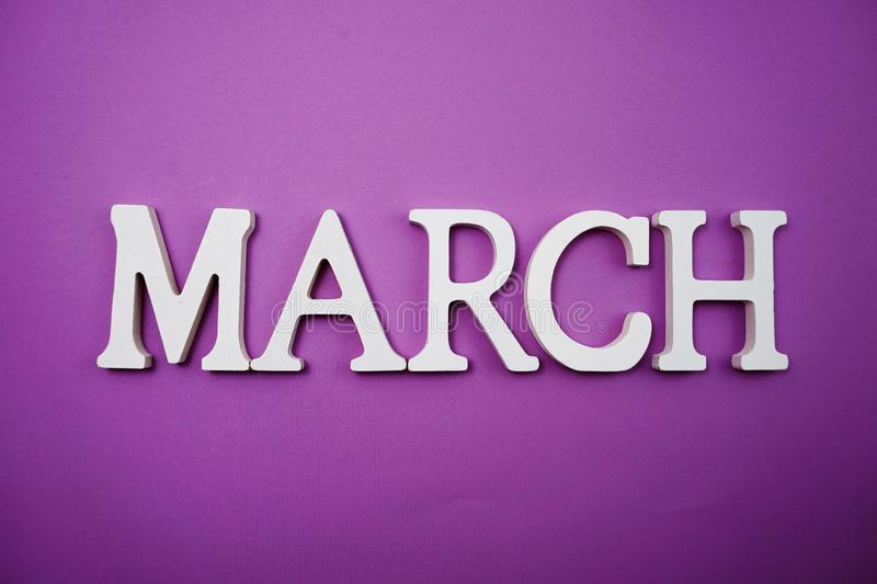 March alphabet letter with space copy on Purple background. Top view of March alphabet letter with space copy on Purple background stock photos