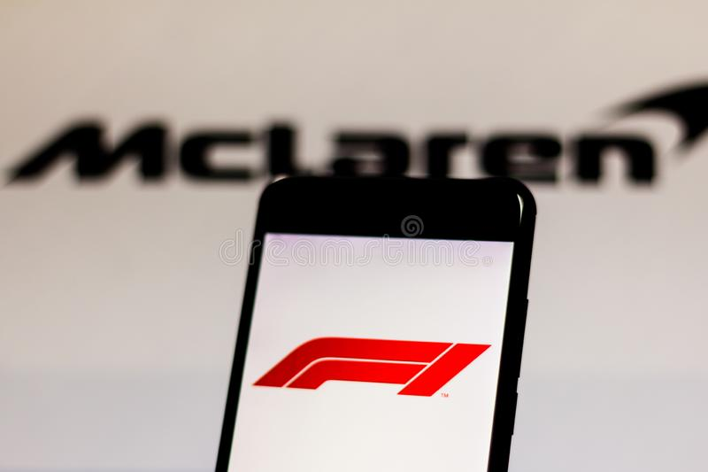 Official F1 FIA Formula 1 logo on the mobile device screen. Team McLaren F1 Team logo on background royalty free stock photos