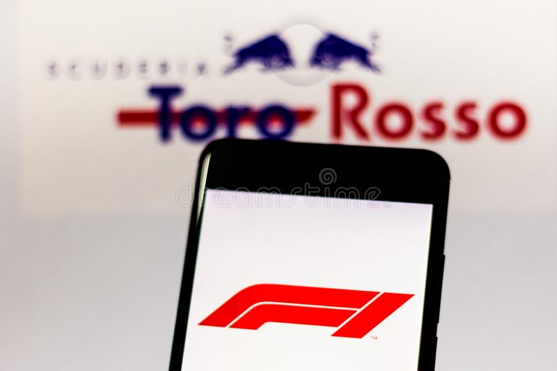 Official F1 FIA Formula 1 logo on the mobile device screen. Team logo Red Bull Toro Rosso Honda in the royalty free stock images