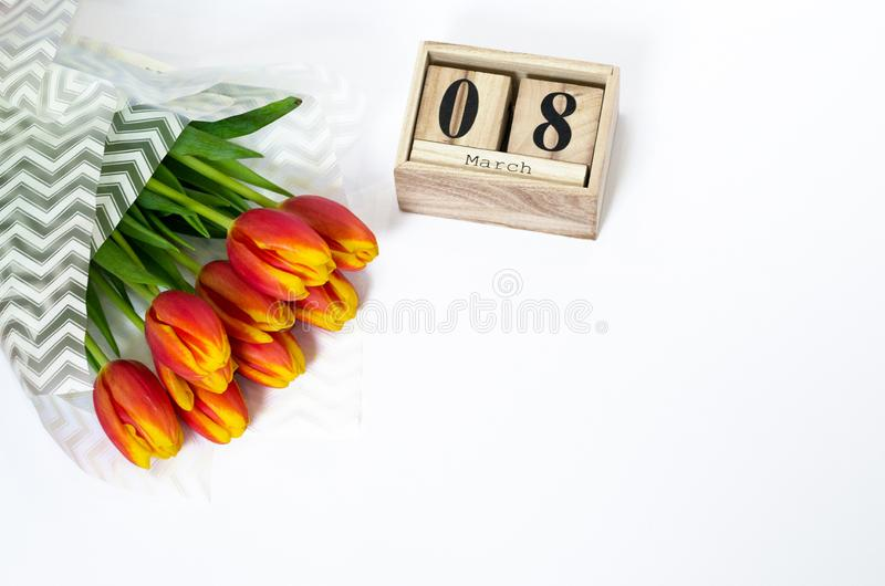 8 March composition on white background. Wooden cubic calendar, bouquet of red flowers, copy space, top view, flat lay. Concept of. Beauty blog, magazine royalty free stock photography