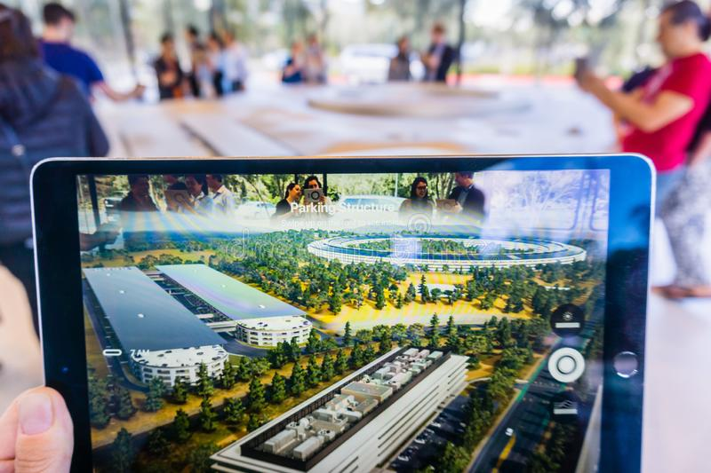 March 8, 2018 Cupertino / CA / USA - People at the Apple Park Visitor Center in Silicon Valley explore the new Apple Offices using. A scaled-down replica of the royalty free stock photo