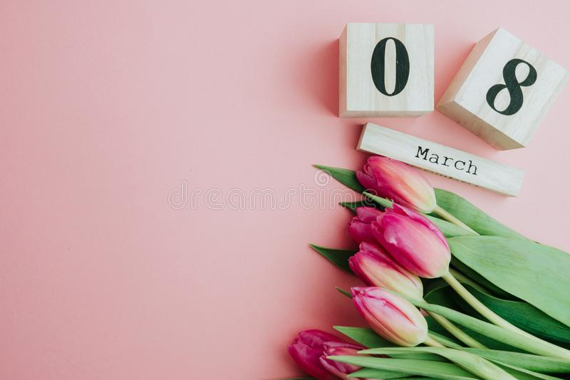 8 March Happy Women`s Day concept. With wooden block calendar and pink tulips on pink background. Copy space. 8 March Happy Women`s Day concept. With wooden stock image