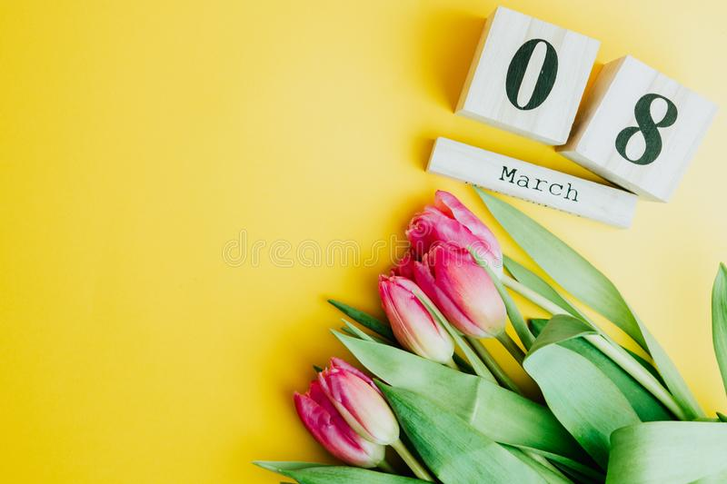 8 March Happy Women`s Day concept. With wooden block calendar and pink tulips on yellow background. Copy space. 8 March Happy Women`s Day concept. With wooden stock photo