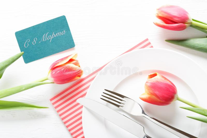 8 march happy womens day. White tulips, a cup of morning coffee and a gift box on the table royalty free stock image