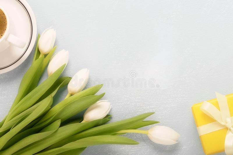 8 march happy womens day. White tulips, a cup of morning coffee and a gift box on the table royalty free stock photo