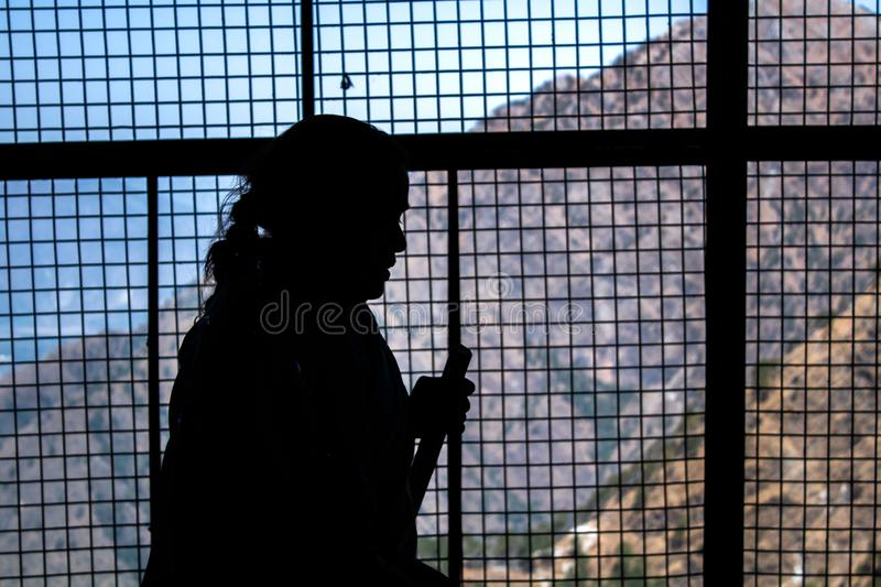 March, 2107 at Jammu - Silhouette of A pilgrim woman walking to the holy shrine of vaishno devi temple holding a stick for walking. Silhouette of an Indian lady royalty free stock photo