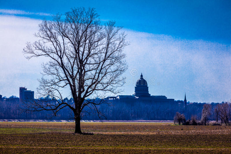 MARCH 4, 2017 - JEFFERSON CITY - MISSOURI - Missouri state capitol building in Jefferson City - seen from farm field and tree in f. Oreground royalty free stock photo