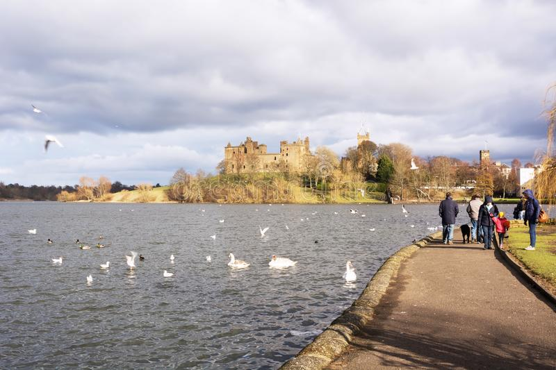 Families enjoying spells of sunny weather beside Linlithgow Loch at Linlithgow Palace in Scotland, United Kingdom royalty free stock photo