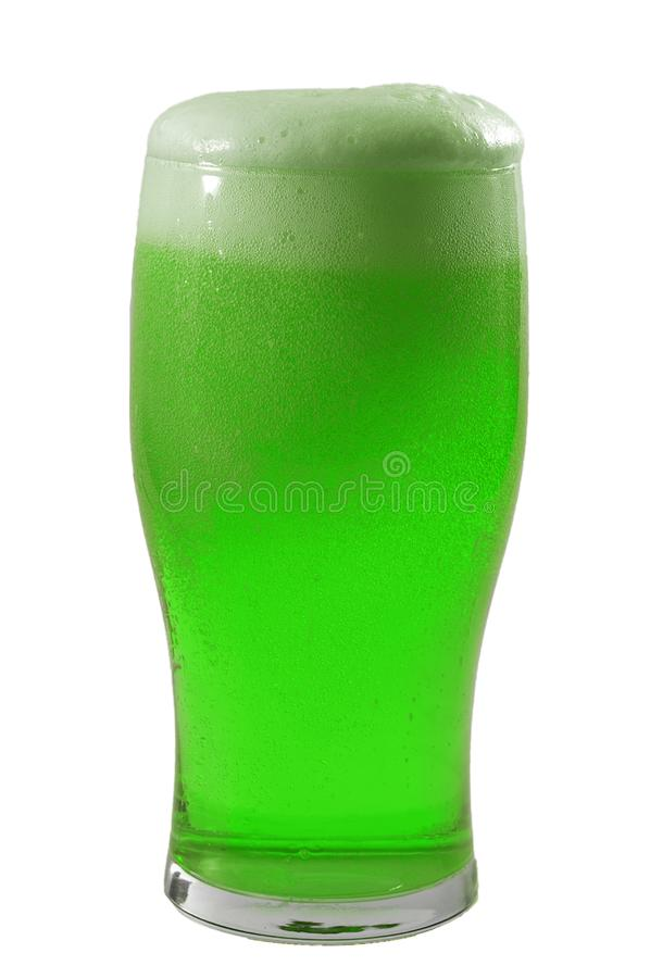 March meme and Happy St patrick`s day concept with frosty glass of frothing green beer and the froth almost spilling over the stock photography