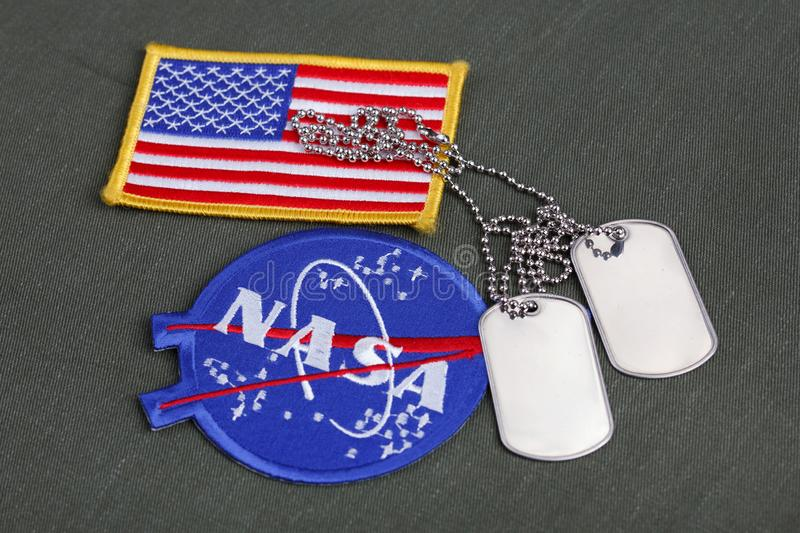 15 March 2018 - The National Aeronautics and Space Administration (NASA) emblem patch and dog tags on green uniform stock photography