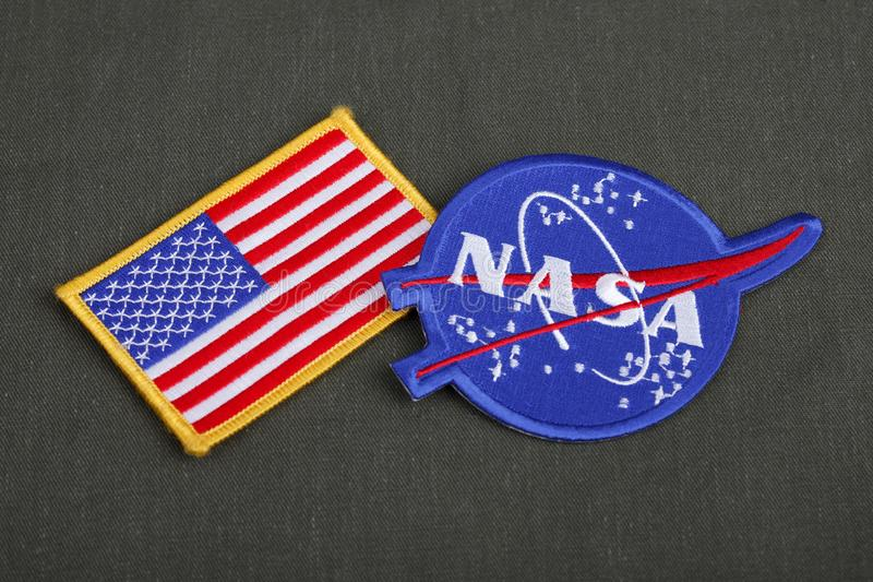 15 March 2018 - The National Aeronautics and Space Administration (NASA) emblem patch and US Flag patch on green uniform stock photography