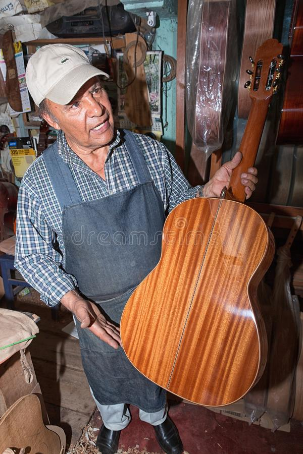 Luthier in Paracho Mexico holding up a guitar in his shop royalty free stock photography