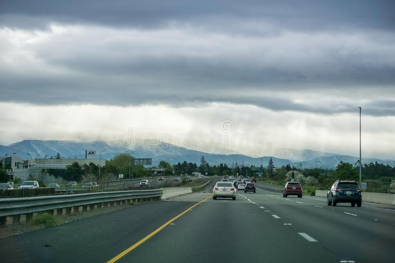 March 26, 2017 San Jose/CA/USA - Driving on the freeway through Silicon Valley on a stormy spring day; rays of light and rain in. The distance royalty free stock photos