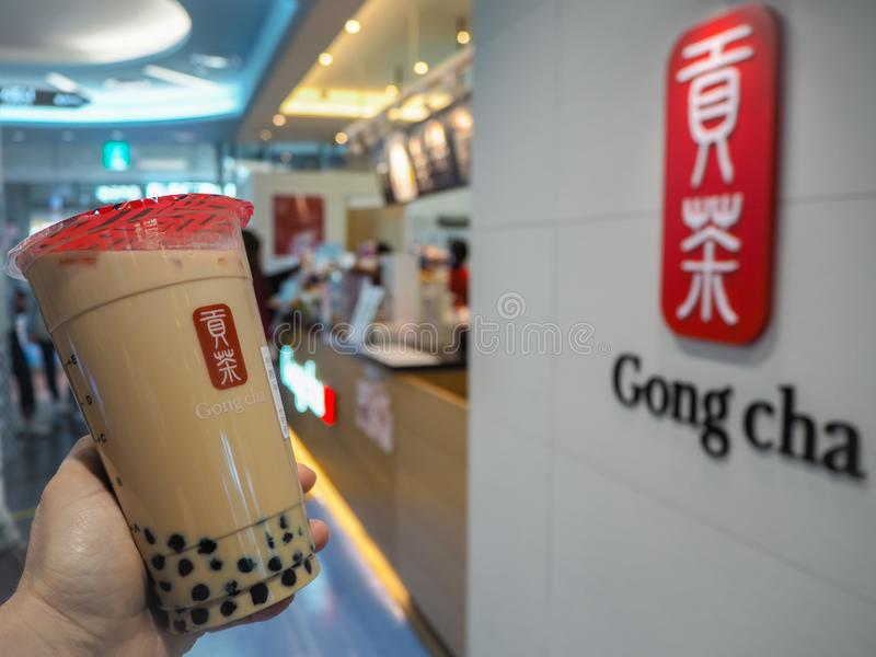 March 2019 - South Korea: Caucasian female hand holding a jumbo size black milk tea with pearls from Gongcha stock image