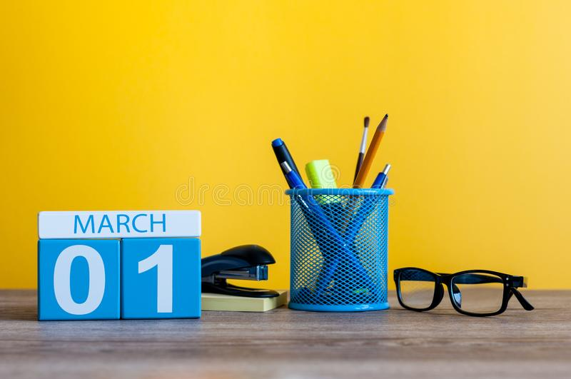 March 1st. Day 1 of march month, calendar on table with yellow background and office or school supplies. Spring time royalty free stock photos
