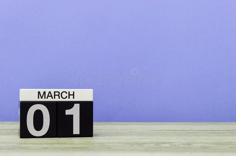 March 1st. Day 1 of march month, calendar on violet background. Spring time, empty space for text, mockup royalty free stock photo