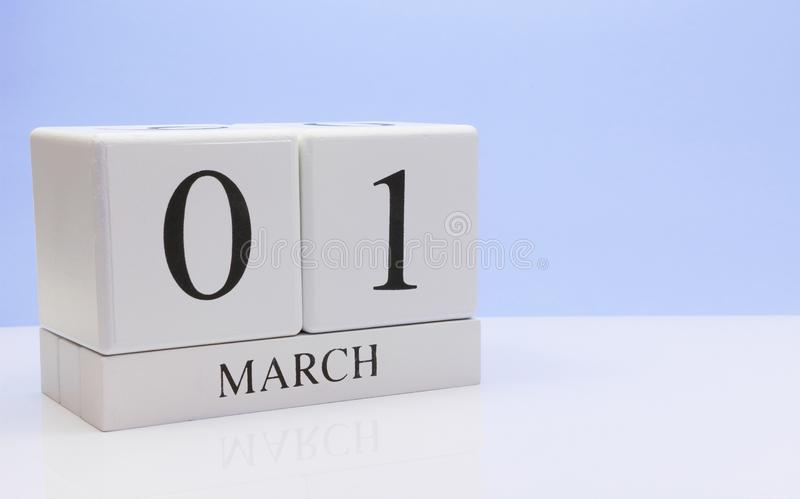 March 01st. Day 01 of month, daily calendar on white table with reflection, with light blue background. Spring time, empty space stock image