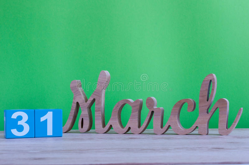March 31st. Day 31 of month, daily wooden calendar on table and green background. Spring time, empty space for text royalty free stock image