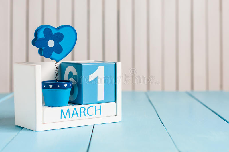 March 1st. Image of march 1 wooden color calendar with flower and heart on white background. First spring day, empty royalty free stock photo