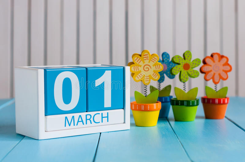 March 1st. Image of march 1 wooden color calendar with flower on white background. First spring day, empty space for stock photos