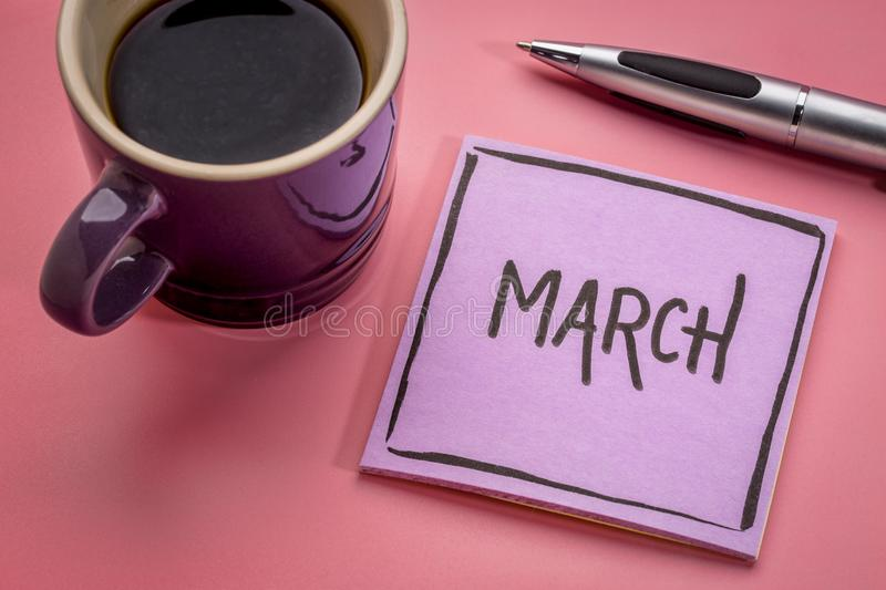 March on sticky note with coffee. March - handwriting in black ink on a sticky note with a cup of coffee stock photos