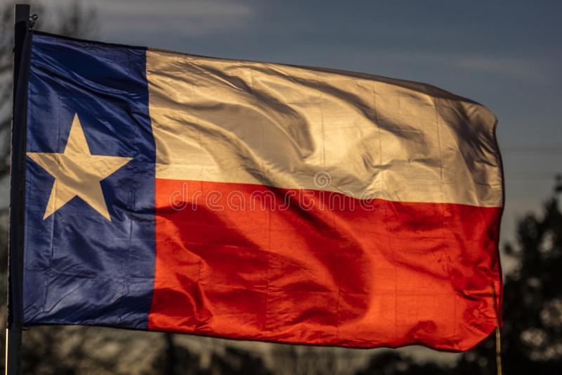 MARCH 6, 2018 - TEXAS STATE FLAG - Texas Lone Star flag stands out against a cloudless blue. Waving, Blue royalty free stock images