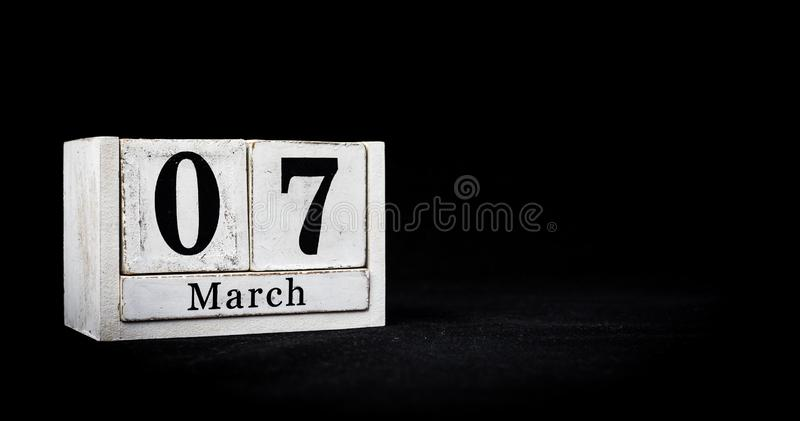 March 7th, Seventh of March, Day 7 of month March - white calendar blocks on black textured background with empty space for text royalty free stock photography