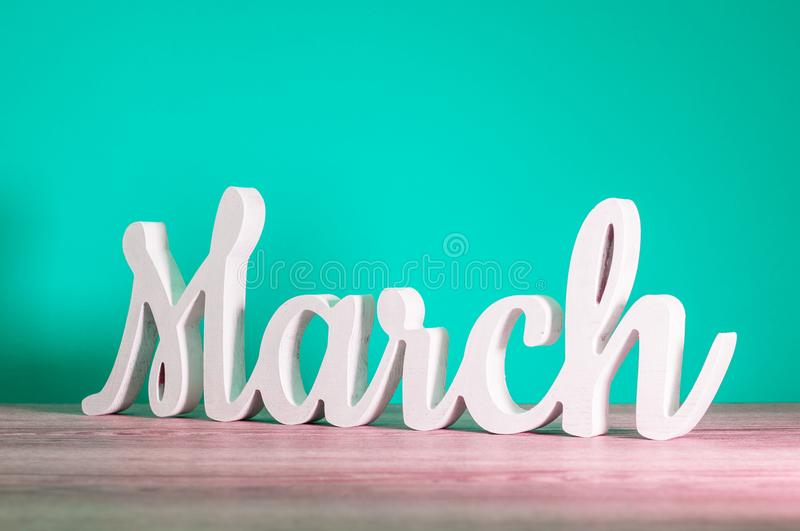 March - wooden carved letters. Beginning of march month, calendar on light turquoise background. Spring coming royalty free stock photos