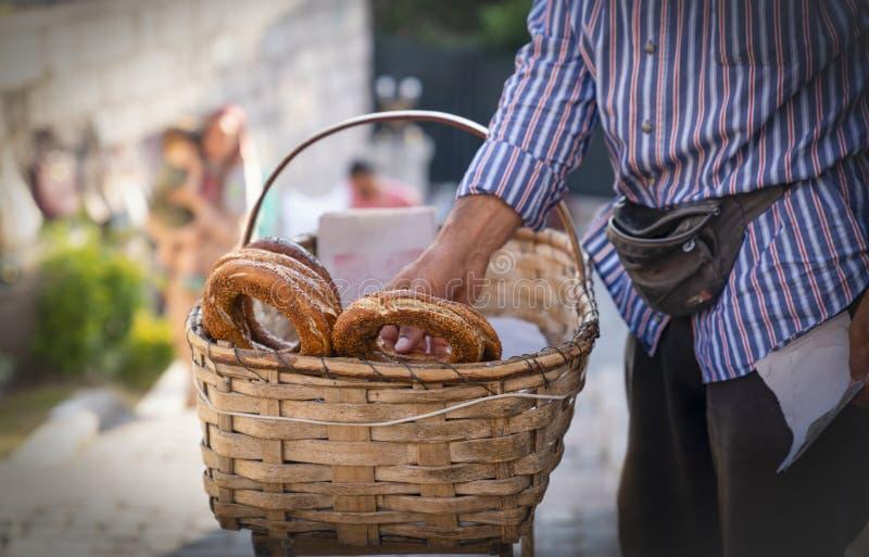 Marchand ambulant vendant le pain de simit avec les graines de s?same dans le panier et tenant l'une d'entre elles pour donner le image libre de droits