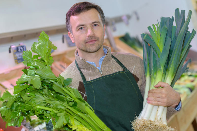 Marchand de légumes de portrait tenant les poireaux et le céleri image libre de droits