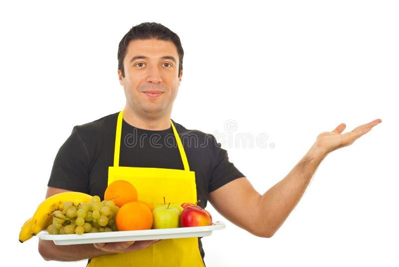 Marchand de légumes de sourire effectuant la présentation images stock