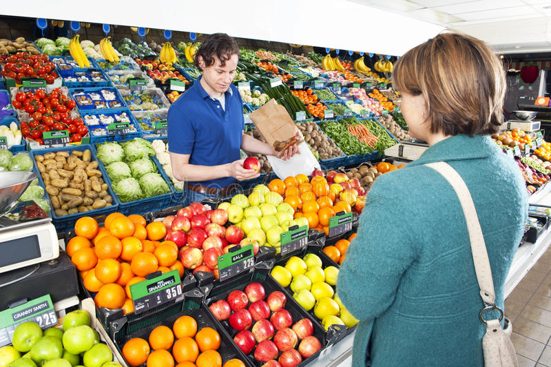 Marchand de légumes servant un propriétaire images libres de droits