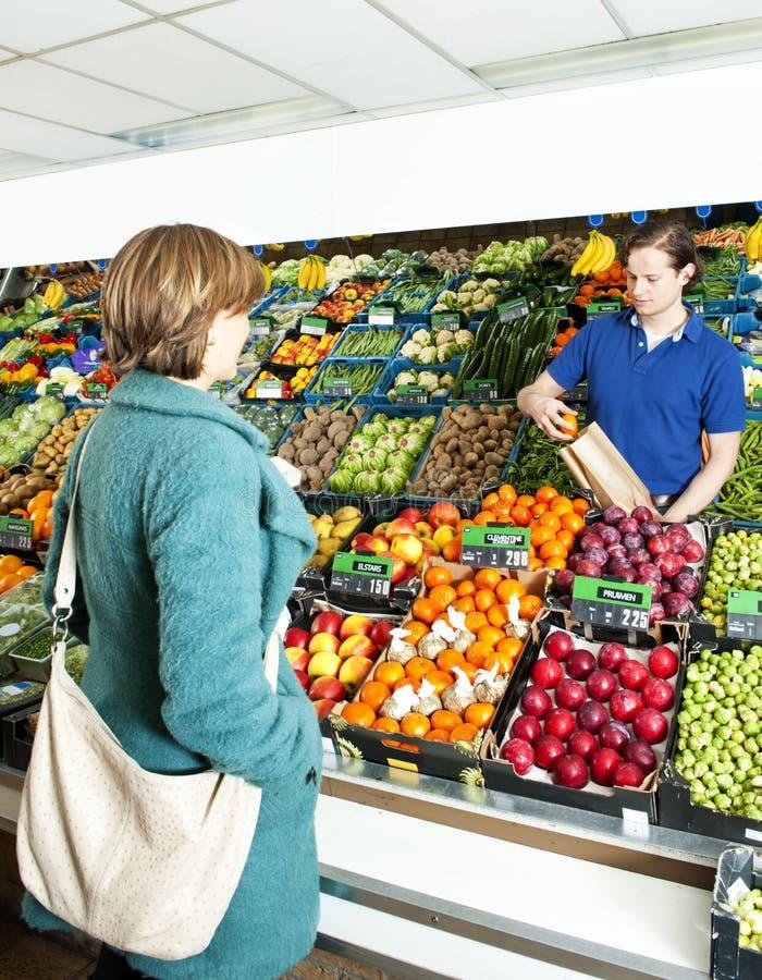 Marchand de légumes servant un propriétaire images stock