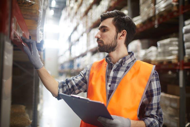 Marchandises de révision de travailleur d'entrepôt photographie stock libre de droits