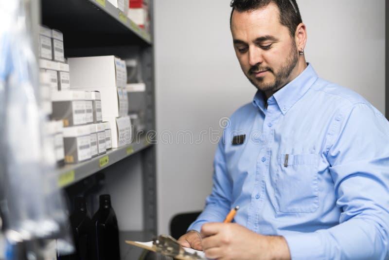 Marchandiseur examinant la disponibilité de produits pour assurer la réparation de voiture image libre de droits